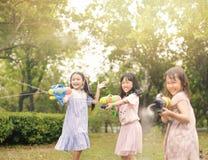 Meisjes die met waterkanonnen spelen op de zomer stock afbeeldingen