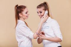 Meisjes die mobiele telefoons met behulp van die lezingsbericht spreken Stock Foto's