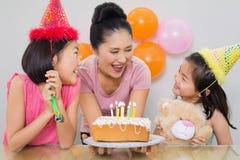 Meisjes die moeder met cake bij een verjaardagspartij bekijken Stock Afbeeldingen