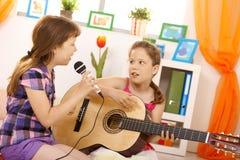 Meisjes die muziek en het zingen spelen Stock Foto