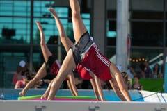 Meisjes die Oefeningen op Drijvende Geschiktheidsmat doen in een Openlucht Zwembad Royalty-vrije Stock Foto's