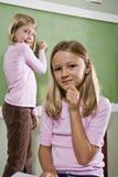 Meisjes die op bord in klaslokaal schrijven royalty-vrije stock afbeelding