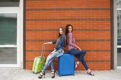 Meisjes die op de treinzitting wachten op de koffer Stock Afbeeldingen