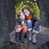 2 meisjes die op een boomstam zitten Stock Foto