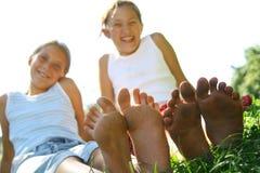 Meisjes die op gras in de zomer worden gezeten Royalty-vrije Stock Fotografie