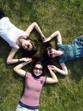 Meisjes die op gras leggen Stock Afbeeldingen