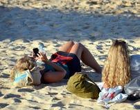 Meisjes die op het strand leggen en op het overzees letten Royalty-vrije Stock Fotografie