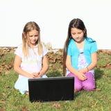 Meisjes die op notitieboekje letten Stock Afbeeldingen