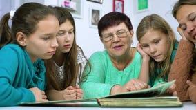 Meisjes die op oud fotoalbum met hun grootmoeder letten stock video