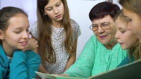 Meisjes die op oud fotoalbum met hun grootmoeder letten stock videobeelden
