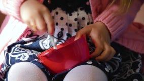 Meisjes die op stoel het spelen met een rode plastic kop zitten Het proces van spijkers Het spel van kinderen in de ruimte stock videobeelden