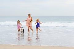 2 meisjes die op strand met mamma en hond lopen Het gelukkige Lopen van de Familie Royalty-vrije Stock Afbeeldingen