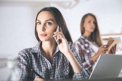 Meisjes die op telefoon in bureau spreken Stock Fotografie