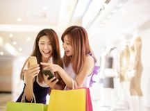 Meisjes die op telefoon letten en in de wandelgalerij winkelen royalty-vrije stock afbeelding