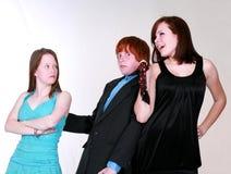 Meisjes die over blozende tienerjongen vechten Royalty-vrije Stock Foto's
