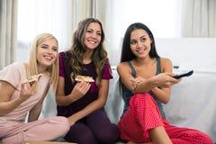Meisjes die pizza eten en op TV letten Stock Foto's