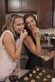 Meisjes die pret hebben terwijl het maken van koekjes Stock Afbeeldingen