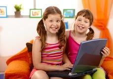 Meisjes die pret met laptop hebben Stock Foto's
