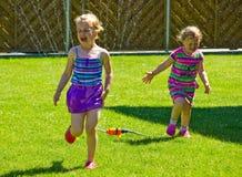 Meisjes die pret met sproeier in tuin hebben Stock Afbeelding