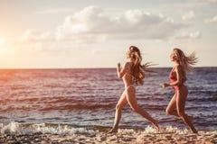 Meisjes die pret op strand hebben stock afbeelding