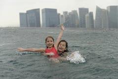 Meisjes die pret in zwembad hebben Stock Foto's