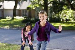 Meisjes die samen buitenhuis spelen stock fotografie