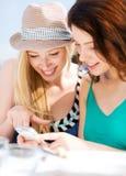 Meisjes die smartphone in koffie bekijken Stock Foto's