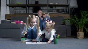 Meisjes die terwijl ouders die op bank rusten schilderen stock videobeelden