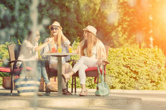 Meisjes die van cocktails in een openluchtkoffie, vriendschapsconcept genieten Stock Foto