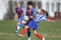 Meisjes die voor bal tijdens voetbalspel vechten Stock Afbeelding