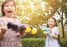meisjes die waterkanonnen in het park spelen stock fotografie
