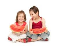 Meisjes die watermeloen eten Stock Afbeelding