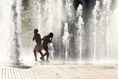 Meisjes die in waterstralen spelen Stock Afbeeldingen