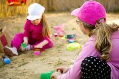 Meisjes die in zandbak spelen Stock Afbeelding
