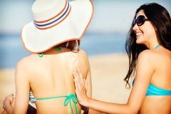 Meisjes die zonroom op het strand toepassen Stock Foto's