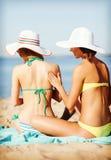 Meisjes die zonroom op het strand toepassen Stock Foto