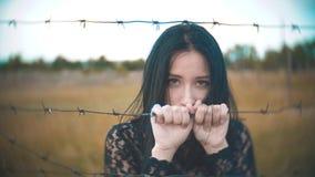 Meisjes donkerbruine vluchteling achter de langzame geanimeerde video van het prikkeldraadkamp de conceptenlevensstijl van vrijhe stock videobeelden