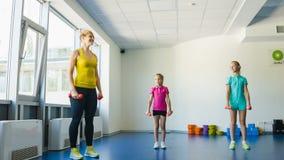Meisjes en Instructeur of moeder die gymnastiek- oefeningen in geschiktheidsklasse doen stock footage