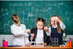 Meisjes en jongen die experiment voorzien van vloeistoffen Reageerbuizen met kleurrijke vloeibare substanties Studie van vloeibar royalty-vrije stock afbeelding