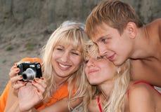 Meisjes en jongen met camera op een strand stock foto