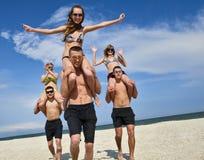 Meisjes en kerels bij het strand Stock Afbeelding