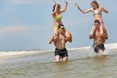 Meisjes en kerels bij het strand Stock Foto's