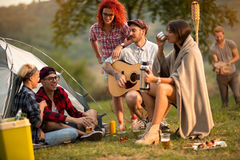 Meisjes en kerels die op zonsondergang in kamp socialiseren Royalty-vrije Stock Afbeeldingen
