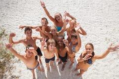 Meisjes en kerels op zand op de zomervakantie Royalty-vrije Stock Afbeeldingen