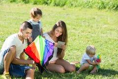 Meisjes en ouders die met vlieger spelen Stock Afbeeldingen