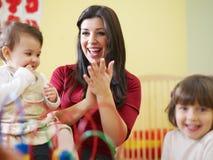 Meisjes en vrouwelijke leraar in kleuterschool royalty-vrije stock foto's