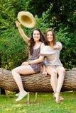 Meisjes frinds zitting op een boomstam die hoeden werpen Royalty-vrije Stock Afbeeldingen