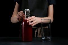 Meisjes gietend sap in glas op donkere achtergrond Het concept van de de zomerdrank royalty-vrije stock afbeelding