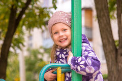 Meisjes glimlachende holding op het metaaltraliewerk van children& x27; s dia's in de werf stock foto's