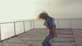 Meisjes in heldere beenkappen professioneel het dansen moderne dans op een houten pijler dichtbij het overzees bij zonsondergang stock video